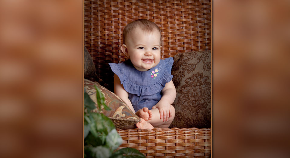 Baby photography: Picture of smiling baby in a brown wicker chair