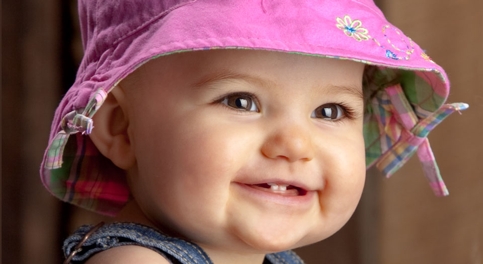 Professional Baby Photography of a baby girl with in a pink bucket hat