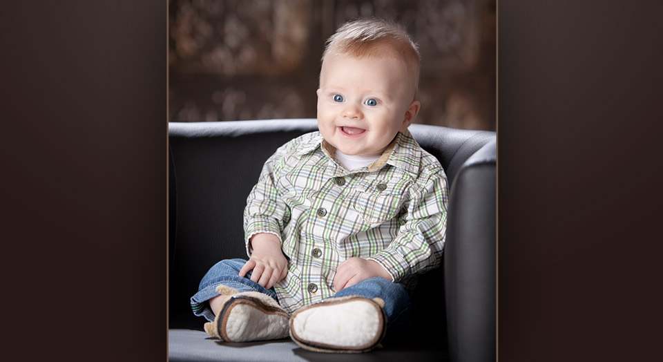 Professional studio baby photography of baby with bright smile