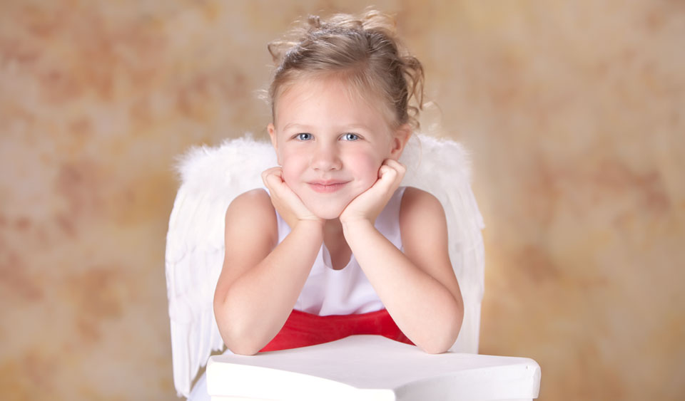 Child photography of a young blonde girl with angel wings