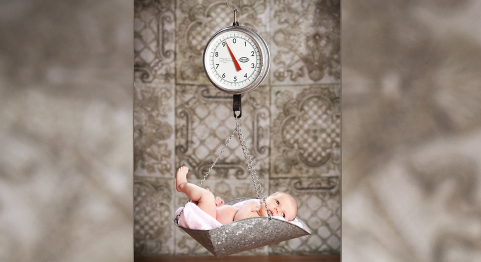 Creative newborn photography in Grandville, Mi of a baby being weighed on by a hanging scale