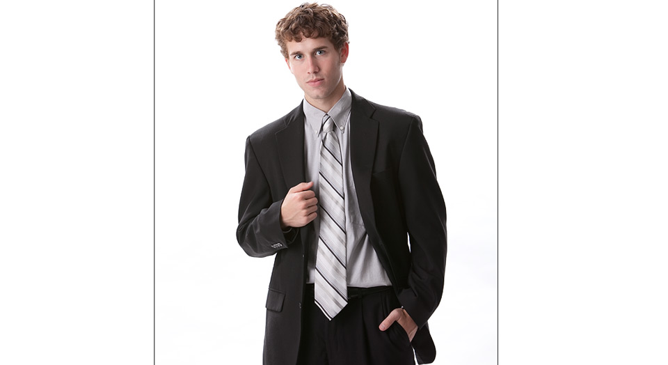 Image of high school senior boy in a relaxed confident pose wearing a suit on high-key white background