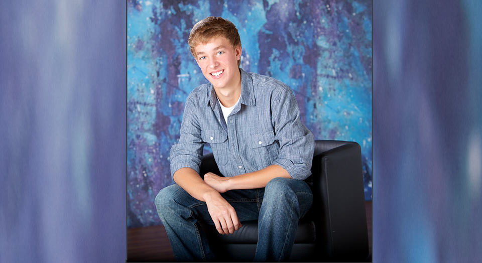 Senior Photography studio setting of a high school senior boy posed sitting on the back of a small black leather chair